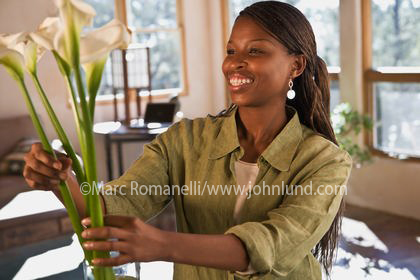 black woman arranging a flower bouquet in her home